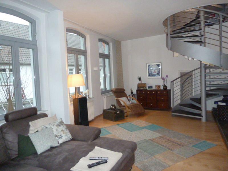 Wohnzimmer mit stylischer Wendeltreppe zur zweiten Ebene der Wohnung in Varel